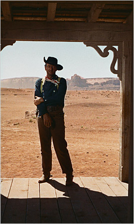 """John Wayne standing in a doorway shot from John Ford's """"The Searchers"""""""