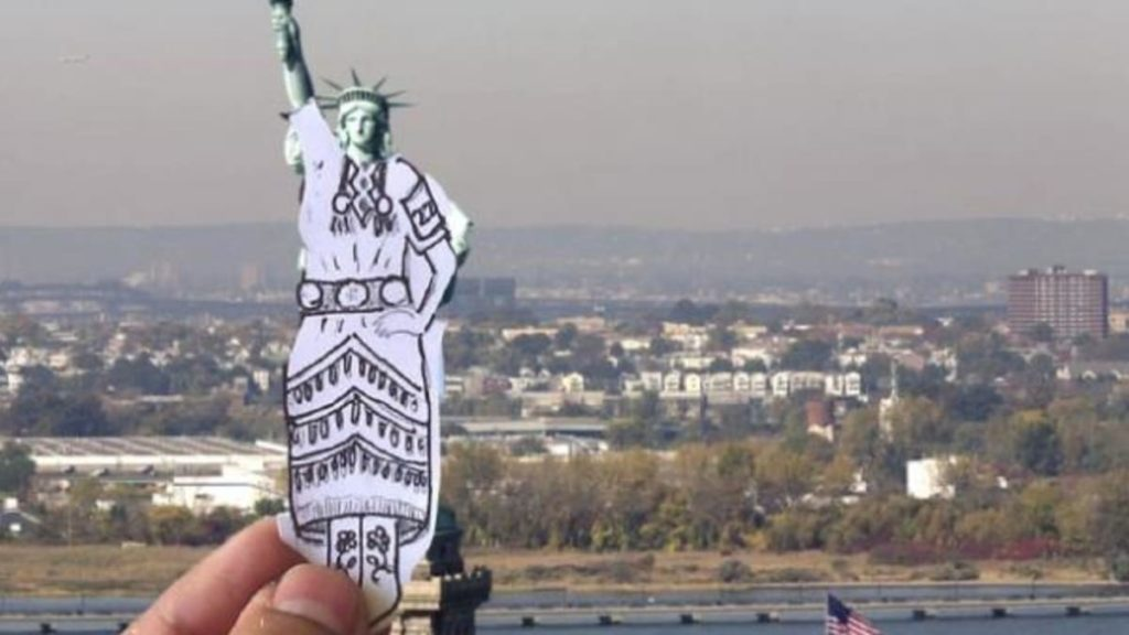 A photo of an ink drawing of a jingle dress held in front of the statue of liberty